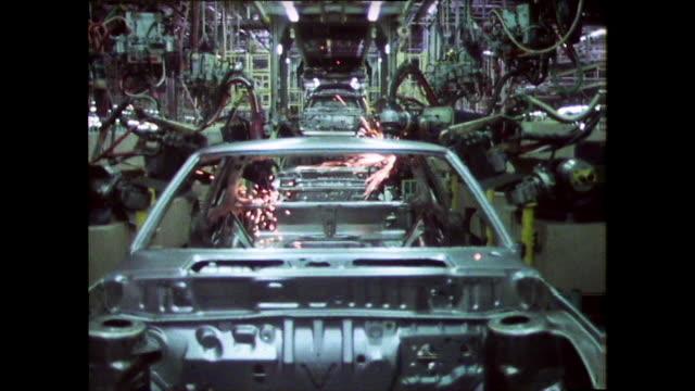 vidéos et rushes de robotic arms weld cars on a production line; 1980 - chaîne de production