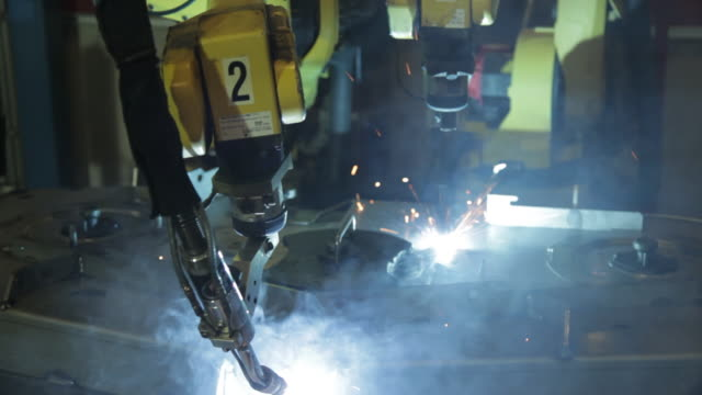 robotic arms weld steel parts in a us manufacturing plant creating sparks and smoke. - metal industry stock videos and b-roll footage