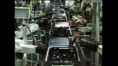 vidéos et rushes de robotic arms welding cars on uk production line; 1986 - chaîne de production