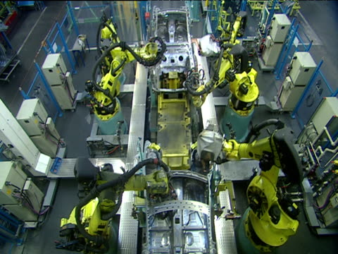 Robotic arms work on hollow chassis of cars on mechanic production line sending sparks flying