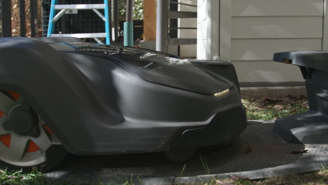 robotic automower driving into its docking station to recharge batteries - grass stock videos & royalty-free footage