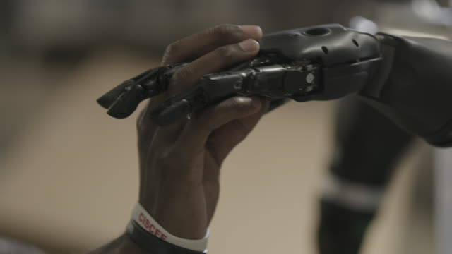 robotic hand holds human hand - prosthetic equipment stock videos & royalty-free footage