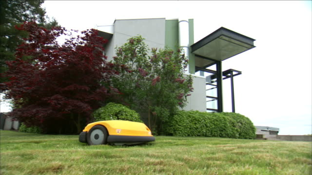a robotic lawn mower cuts grass near a modern home. - landscaped stock videos & royalty-free footage