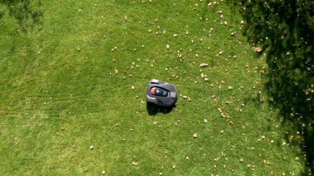 robotic lawn mower moving across lawn from aerial view - landscaped stock videos & royalty-free footage