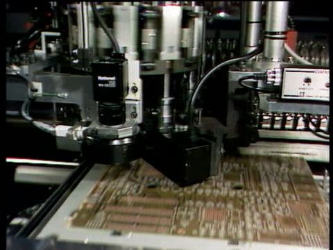 robotic machine stamping electronic components into computer microchip circuit board - computer chip stock videos & royalty-free footage