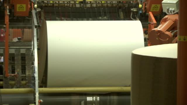 vidéos et rushes de a robotic machine wraps a large roll of paper. - fabrique de papier