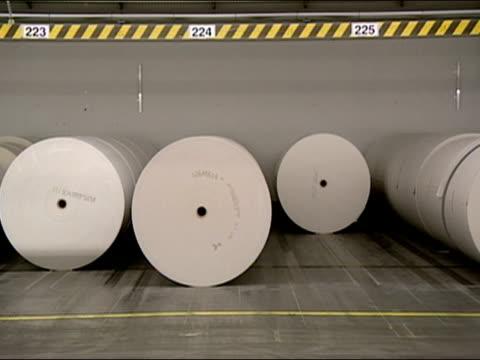 Robotic pallet trucks gliding past paper rolls in paper factory