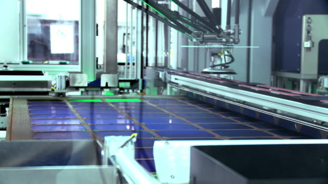 CU ZI Robotic spiders picking solar cells out of large panel and dropping them onto conveyor belt at solar manufacturing plant Solarworld, Hillsboro, Oregon, USA