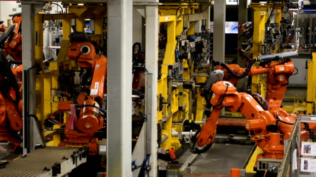 robotic systems work on the chassis of a car during an automated stage of production at the jaguar land rover factory on march 1 2017 in solihull... - fahrgestell stock-videos und b-roll-filmmaterial