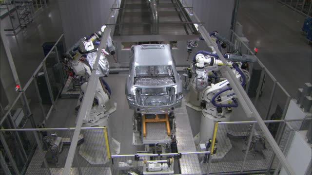 Robots flank an automotive assembly line.