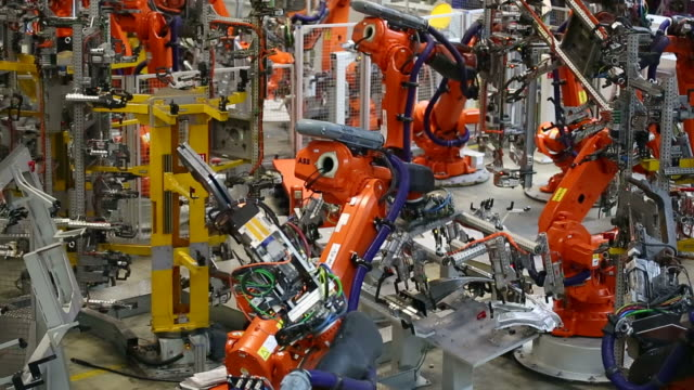 vidéos et rushes de robots moving a part of a car body - industrie