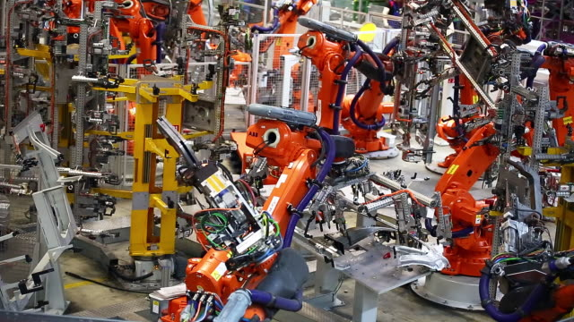 stockvideo's en b-roll-footage met robots moving a part of a car body - metaalindustrie