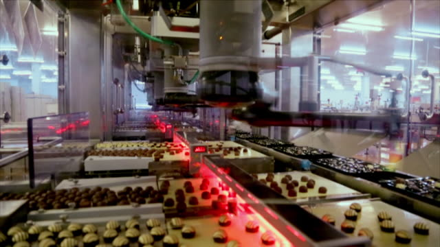 robots packing different shaped chocolates into trays for chocolate boxes - food processing plant stock videos and b-roll footage