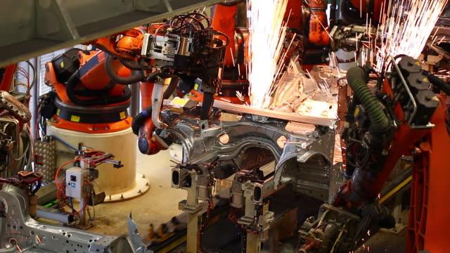 vidéos et rushes de robots welding on car body - usine automobile