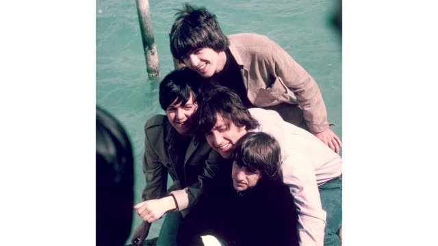 "rock and roll band ""the beatles"" pose for a portrait in front of water with wind blown hair on the set of the movie ""help!"" which was released on... - hair band stock videos & royalty-free footage"