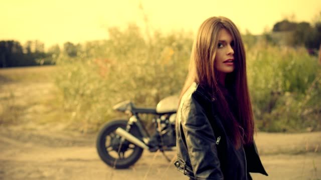 Rock And Roll Frau. Posiert mit Motorrad