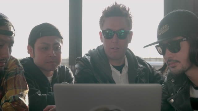 rock band crew checking their picture on laptop. - 20代点の映像素材/bロール