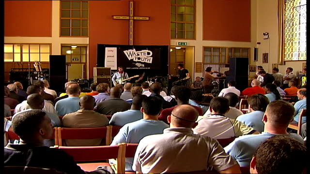 Rock band Dirty Pretty Things play gig in Pentonville Prison INT The Enemy performing on stage then back view of prison audience applauding SOT