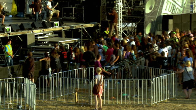 A rock band performs on the main state at an outdoor music festival as fans listen.