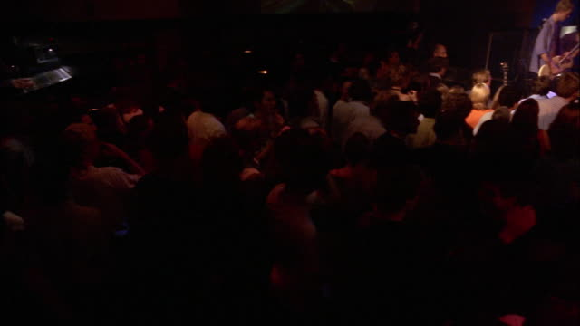 A rock band plays in a small, crowded club near a screen showing abstract psychedelic videos.