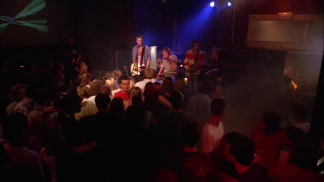 A rock band plays under flashing lights in a small, crowded club.