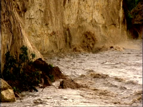 vidéos et rushes de ms rock breaking away from rock face due to erosion from muddy flood water flowing down river, mana pools, zimbabwe - érodé