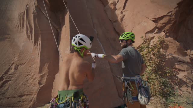 Rock climber and belayer fist bump as they prepare for ascent.