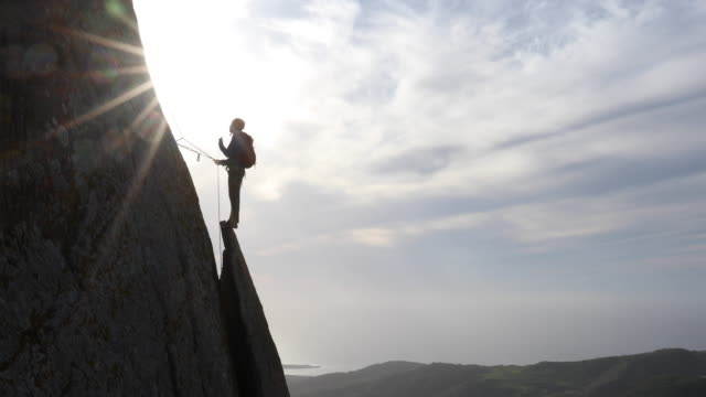 Rock climber ascends above vertical rock flake