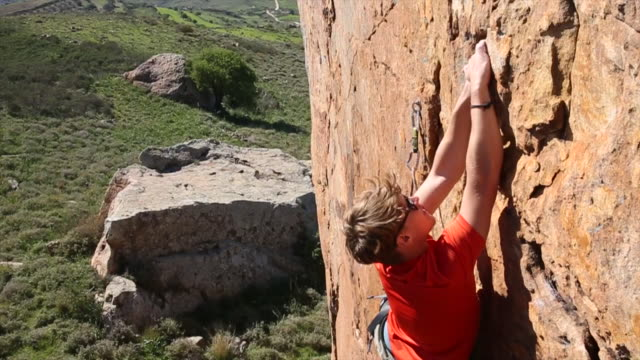 Rock climber ascends difficult overhanging face above hills, sea