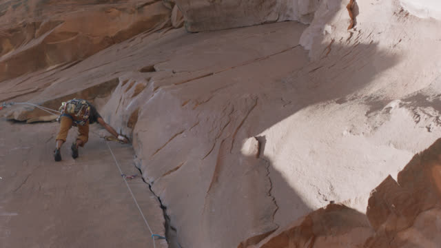 rock climber carefully rappels down steep sandstone rock face. - rock face stock videos & royalty-free footage