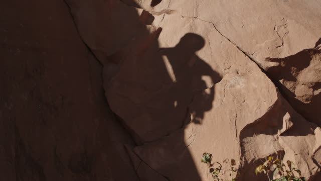 rock climber casts shadow on sandstone rock face. - high up stock videos & royalty-free footage