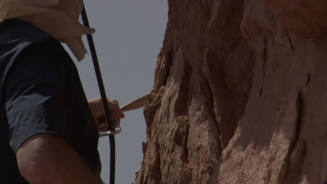 a rock climber checks a carabiner as he prepares to ascend. - challenge stock videos & royalty-free footage