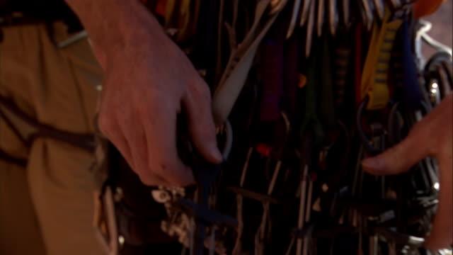 vídeos de stock, filmes e b-roll de a rock climber checks the equipment on his harness. - gancho de alpinismo