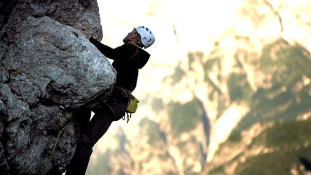 stockvideo's en b-roll-footage met hd: rock climber climbing the cliff - sporthelm