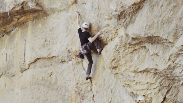 Rock climber clipping his rope into the next bolt