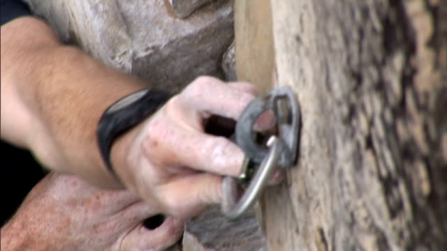 a rock climber clips carabiners to a rock face. - カラビナ点の映像素材/bロール