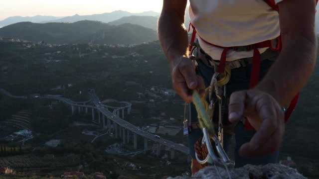 rock climber clips protection, takes smart phone pic over valley - imbracatura di sicurezza video stock e b–roll
