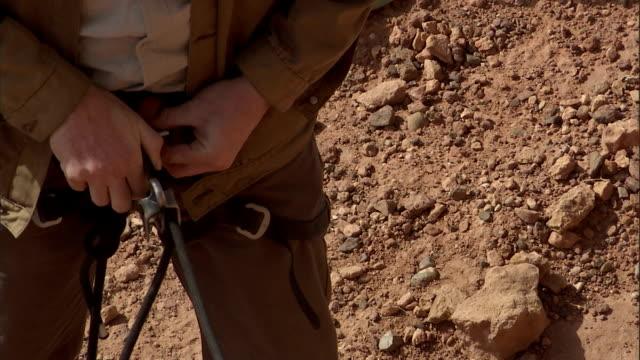vidéos et rushes de a rock climber detaches a carabiner from his harness and releases a rope. - harnais de sécurité