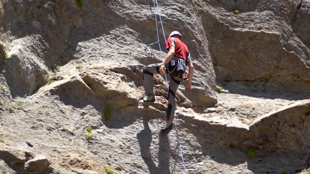 a rock climber falling and being saved by his rope. - slow motion - felsklettern stock-videos und b-roll-filmmaterial