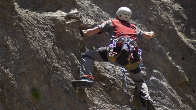 A rock climber falling and being saved by his rope.