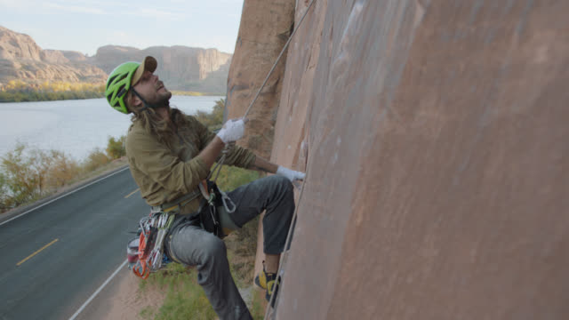 slo mo. rock climber falls and catches himself with belaying rope on steep sandstone rock face over utah road. - near miss stock videos and b-roll footage