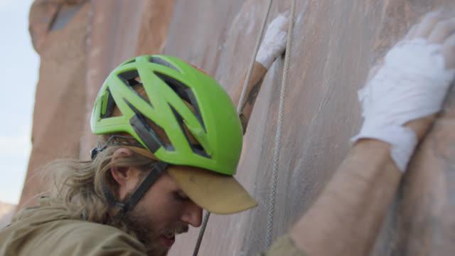 vidéos et rushes de slo mo. rock climber finds handholds to pull himself up steep sandstone rock face. - rock face