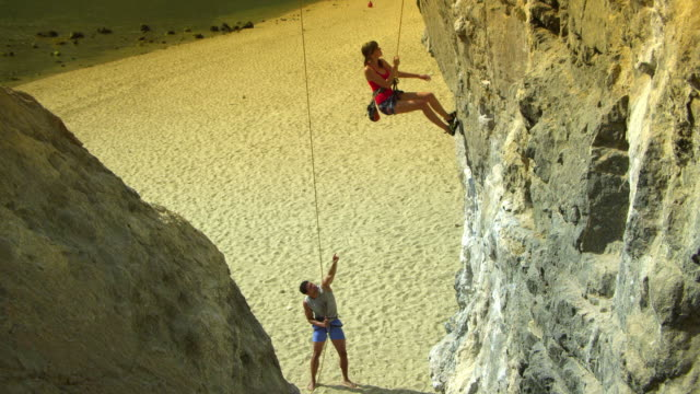 ha ws rock climber hanging from rope off rock face, man standing on beach belaying / krabi, thailand - imbracatura di sicurezza video stock e b–roll