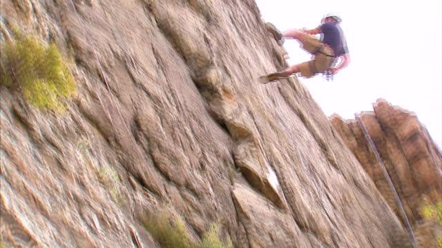 ws la pan rock climber jumping across face of mountain / provo, utah, usa - provo stock videos & royalty-free footage