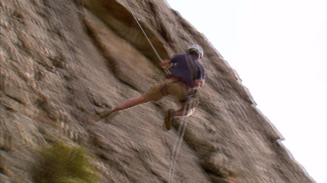 ws la pan rock climber jumping across face of mountain / provo, utah, usa - rock face stock videos & royalty-free footage