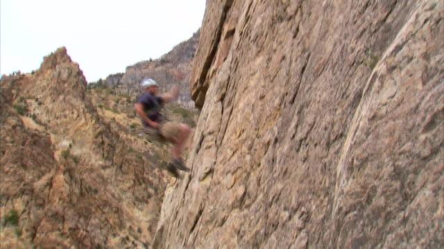 ws la pan rock climber jumping across face of mountain / provo, utah, usa - rock face stock videos & royalty-free footage