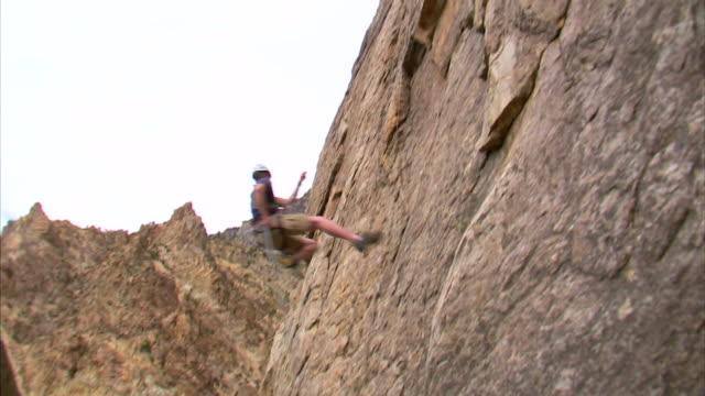 ws pan rock climber jumping across face of mountain / provo, utah, usa - provo stock videos & royalty-free footage