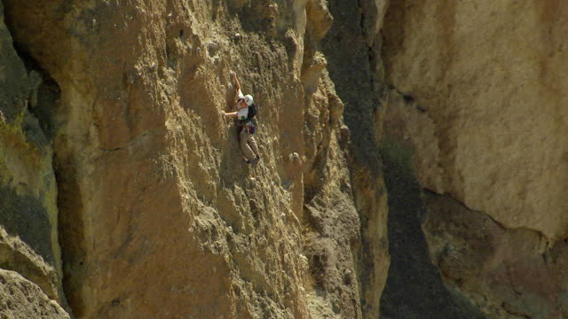MS AERIAL Rock climber looking down during climb / Terrebonne, Oregon, United States