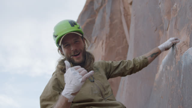 slo mo. rock climber makes shaka sign at camera and cheers on steep sandstone rock face. - gente comune video stock e b–roll