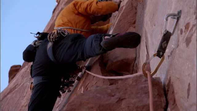 a rock climber moves carefully up a cliff side. - hex climbing equipment stock videos and b-roll footage